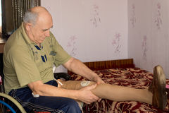 Elderly amputee fitting his artificial leg Stock Images