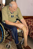 Elderly amputee with a prosthetic leg. Sitting in a wheelchair at home with his trouser leg rolled up while he fits it to his stump Stock Photos