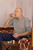 Elderly amputee sitting taking his medication Stock Photos