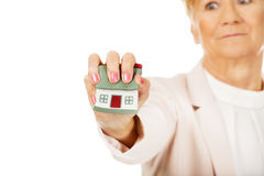 Elderly angry business woman crushed house model Stock Photo