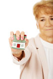Elderly angry business woman crushed house model Royalty Free Stock Images