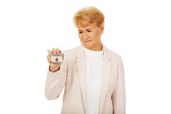 Elderly angry business woman crushed house model Royalty Free Stock Photo