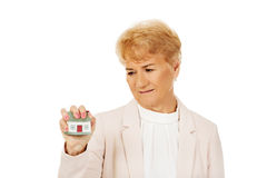 Elderly angry business woman crushed house model Stock Photos