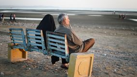 Elderly Arabian couple sit on a bench and look at the sea.  stock footage