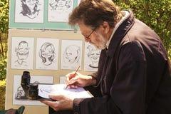 Elderly artist draws cartoons. Burbiskis, Lithuania - May 09, 2015: Elderly artist draws cartoons on holiday in Burbiskis, Radvilisis, Lithuania stock photos