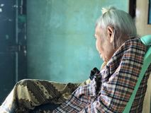 Elderly Asian, Burmese Woman siting with leg crossed on green plastic chair and gazing at distance royalty free stock photography