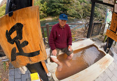 Elderly Asian Man Soaking his feet at a hotspring Stock Photo