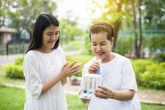 Free Elderly Asian Mother Using Incentive Spirometer Or Three Balls For Stimulate Lungs,Encouragement Daughter Take Care And Support Royalty Free Stock Images - 147727639