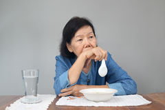 Elderly asian woman bored with food Royalty Free Stock Photos