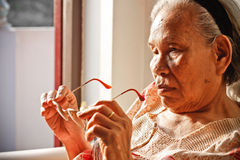 Elderly Asian Woman holding Glasses Stock Photo
