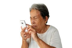 Elderly asian woman are holding and looking mobile phone with poor eyesight isolated on white background royalty free stock photos