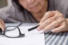 Elderly asian woman repair broken glasses royalty free stock photo