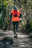 Elderly athlete man running mountain marathon along a forest trail. With a backpack and walking sticks Stock Photos