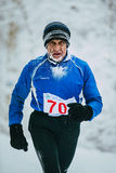 Elderly athlete man running on snowy Park alley. face in frost Stock Photos