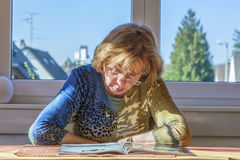 Elderly attractive woman reading in a magazine Royalty Free Stock Images
