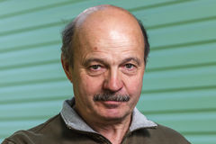 Elderly bald man with a mustache strictly looking directly into the camera Stock Photos