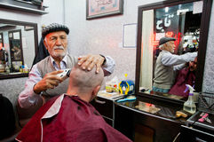 Elderly barber cuts and shaves the client in small hair saloon Stock Images