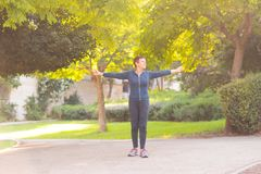 Elderly beautiful active happy woman in the morning in the autumn park doing sports exercises. royalty free stock photos