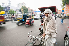 Elderly bicycle rickshaw looking for the passenger on the traffic street Royalty Free Stock Photography