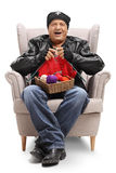 Elderly biker sitting in an armchair and knitting Stock Photo