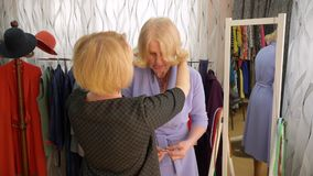 Senior woman is trying on the necklace in the clothes store. Elderly blonde woman is trying on the necklace with stones in the clothes store. Seller consultant stock footage