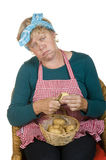 Elderly bored house wife. Is peeling the potatoes stock images
