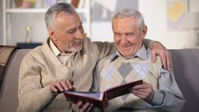 Elderly brothers watching family album on sofa at home, pleasant memories. Stock footage stock video