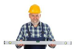 Elderly builder with spirit level tool Stock Image