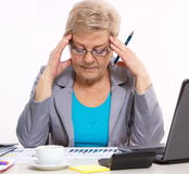 Elderly business woman analyzing financial charts at desk in office, business concept Stock Photo