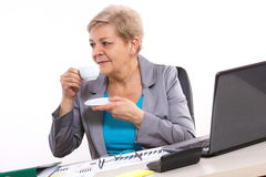 Elderly business woman drinking tea or coffee at desk in office, break at work Royalty Free Stock Photos