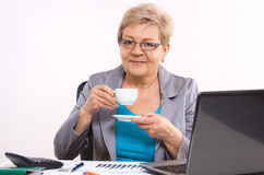 Elderly business woman drinking tea or coffee at desk in office, break at work Royalty Free Stock Images