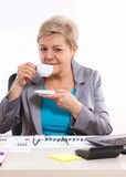 Elderly business woman drinking tea or coffee at desk in office, break at work stock photo