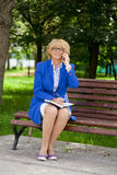 Elderly business woman in jacket sittin on bench with daily log Royalty Free Stock Image