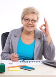 Elderly business woman showing sign ok and working at her desk in office, business concept Royalty Free Stock Images