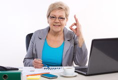 Elderly business woman showing sign ok and working at her desk in office, business concept Royalty Free Stock Image