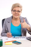 Elderly business woman showing thumbs up and working at her desk in office, business concept Royalty Free Stock Images