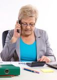 Elderly business woman talking on mobile phone and working at her desk in office, business concept Royalty Free Stock Photos