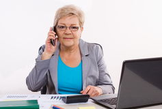 Elderly business woman talking on mobile phone and working at her desk in office, business concept Stock Image