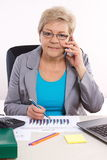 Elderly business woman talking on mobile phone and working at her desk in office, business concept Royalty Free Stock Image