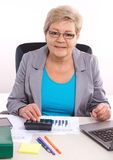 Elderly business woman working at her desk in office, analysis of sales plan, business concept Royalty Free Stock Images