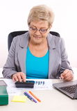 Elderly business woman working at her desk in office, analysis of sales plan, business concept stock photo