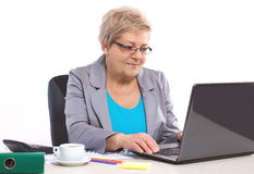 Elderly business woman working with laptop at her desk in office, business concept Stock Images