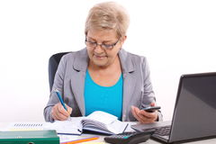 Elderly business woman writing in notebook and working at her desk in office, business concept Stock Images