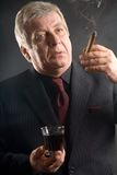Elderly businessman with drink and cigar, smoking Stock Photos