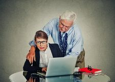 Elderly businessman harassing his young colleague woman Royalty Free Stock Photography