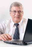 Elderly businessman on laptop, smiling Royalty Free Stock Photography