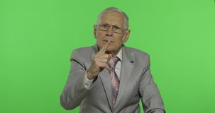 Elderly businessman quarrels at someone threateningly moves with his hand