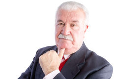 Elderly businessman resting chin on hand Royalty Free Stock Images