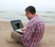 Elderly businessman sitting with notebook on beach Stock Image