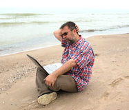 Elderly businessman sitting with notebook on beach Stock Photos